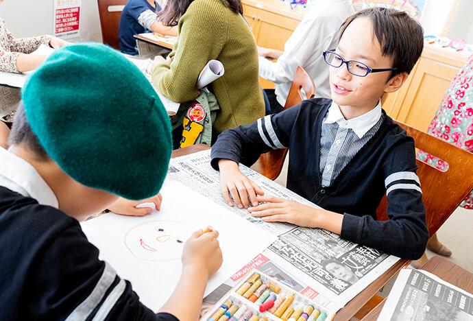 緑のベレー帽を被った男の子と眼鏡をかけた男の子が似顔絵を描きあっている写真