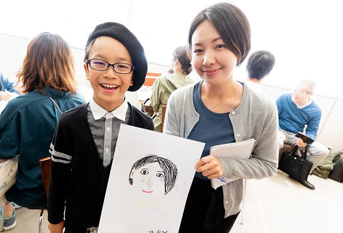 黒のベレー帽を被った男の子が描いた先生の似顔絵と先生との2ショット写真
