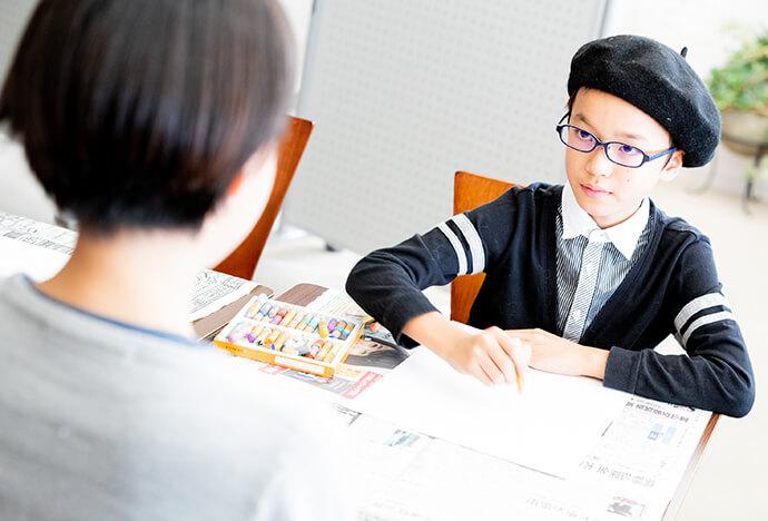 黒いベレー帽を被った男の子が先生の似顔絵を描いている写真