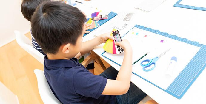 カラーチャートを使う子ども/作った猪の版画にインクを付けて判を試す子どもと