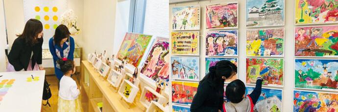 自分で作ったアート作品を見る親子と先生。 展覧会に飾られている絵を親子で見ている。