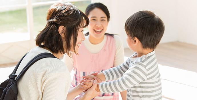 お迎えに来た保護者と子供と保育士
