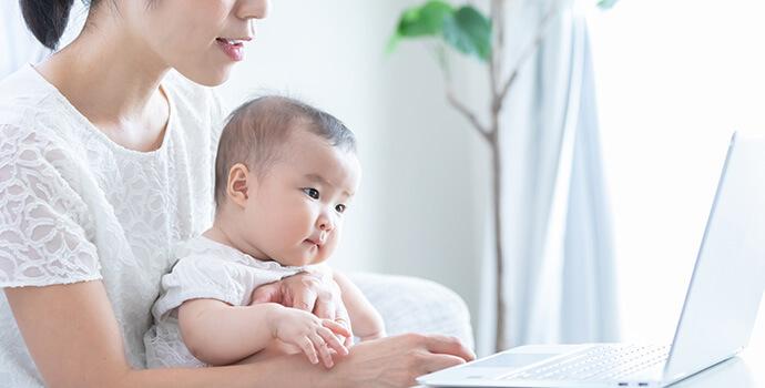 お母さんとパソコンを見つめる赤ちゃん