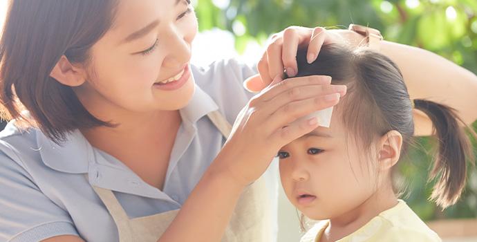 子供の熱を測る保育士
