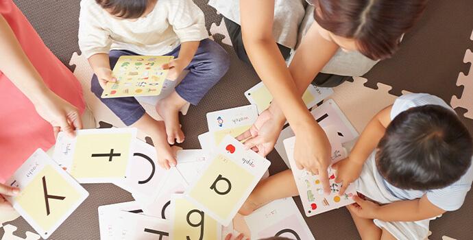 英語カードで遊ぶ子供たちと保育士