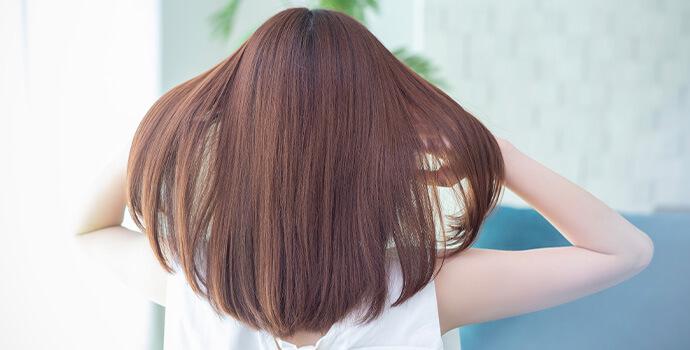 髪を広げる女性の後ろ姿