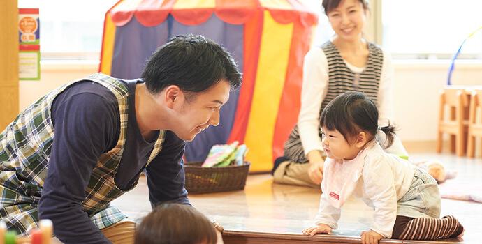 子供の顔を覗き込む男性保育士