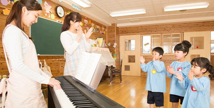 保育士のピアノの伴奏で手遊びをする子供たち