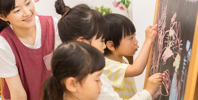 黒板に絵を描く子供たち